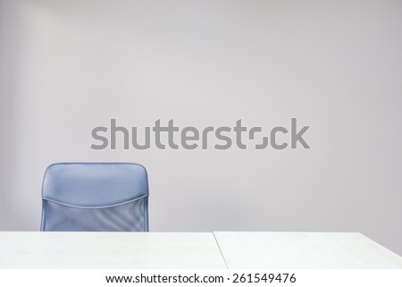 Empty office chair against an empty wall.