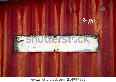 Empty Old painted metal plate tag screwed on red wall - stock photo