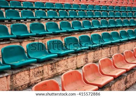 Empty old plastic seats at stadium, open door sports arena. - stock photo