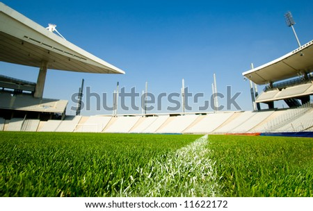 Empty Olympic Stadium shot from dividing line of the green grass soccer field - stock photo