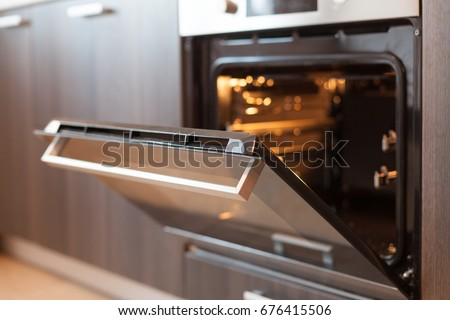 open oven in kitchen. empty open electric oven with hot air ventilation. new oven. door is and in kitchen
