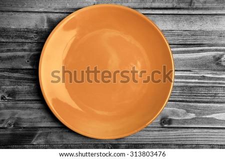 Empty orange plate on gray wooden table - stock photo