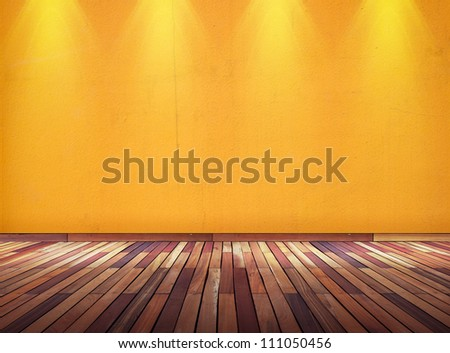 Empty orange wall with spot lights and wooden floor - stock photo