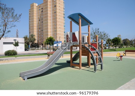 Empty Outdoor Park Playground Slide Equipment in Highrise Urban Suburb Residential Area of Spain Europe - stock photo