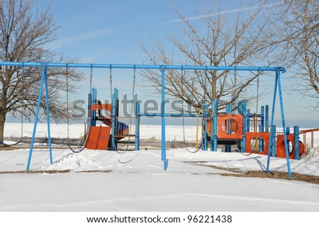 Empty Outdoor Playground Sunny Snow Winter Scene Blue Sky Day on north side of Chicago Illinois along Lake Michigan - stock photo