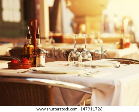 Empty outdoor restaurant table at sunset - stock photo