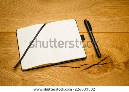 Empty pages of a notebook which is skew on the desk. Marker next to the textbook. - stock photo