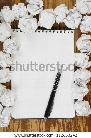 Empty paper, crumpled paper and pen on wooden table - stock photo