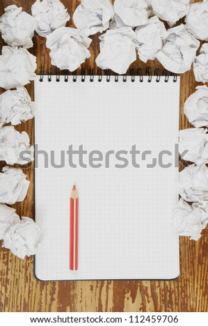 Empty paper, crumpled paper and red pencil on wooden table - stock photo