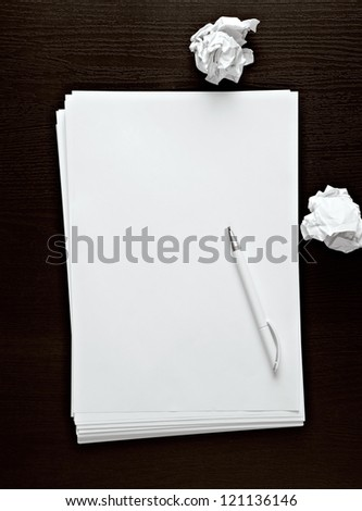 empty paper, crumpled paper and white pen on dark desk - stock photo