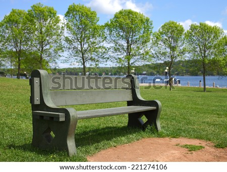 Empty park bench in summer - stock photo