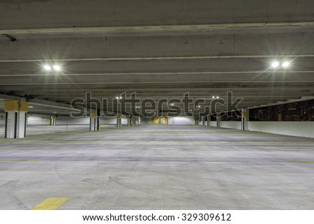 Empty parking garage at night with city panorama