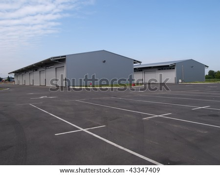 empty parking lot in front of the warehouse - stock photo