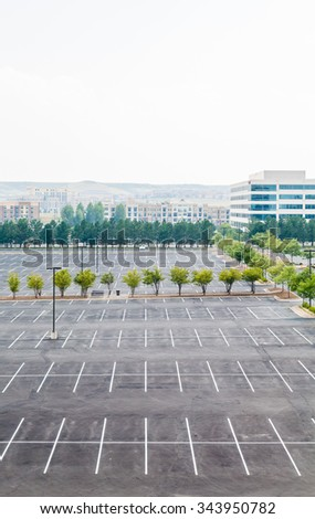 Empty parking lot with one white car in distance - stock photo