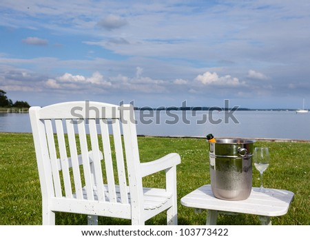 Empty patio chair and champagne in ice bucket by side of the Chesapeake bay