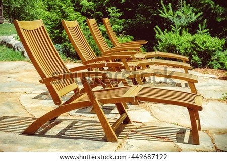 Empty patio with wood chairs lined up and ready for sunbathers at the lake - stock photo