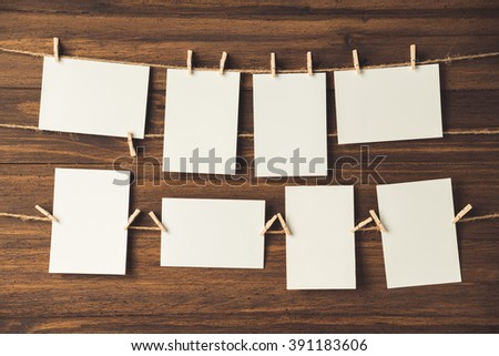 empty photo frames hanging with clothespins on wooden background - stock photo