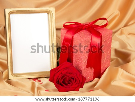 Empty photoframe with gift and red roses on gold fabric - stock photo