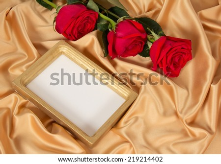Empty photoframe with three red roses on golden textile - stock photo