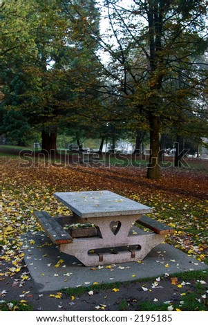 Empty picnic table in the park in the fall. - stock photo