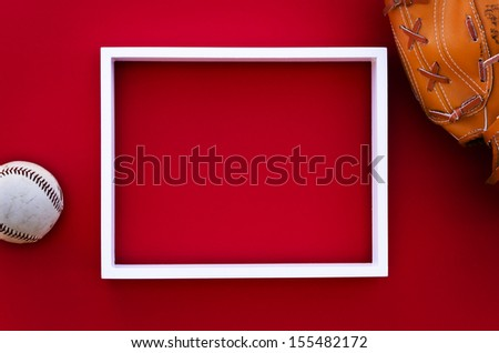 empty picture frame on a red wall with worn baseball glove and ball - stock photo
