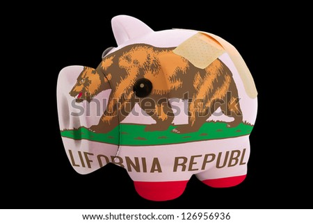 empty piggy rich bank in colors of flag of us state of california on black background - stock photo