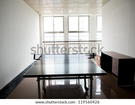 Empty ping pong table near the  windows. - stock photo