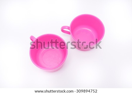 Empty pink plastic cups on white background