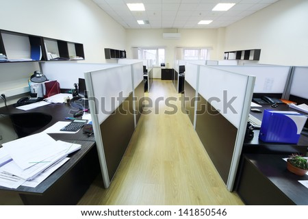 Empty places of work separated by partition with desktops and papers. - stock photo