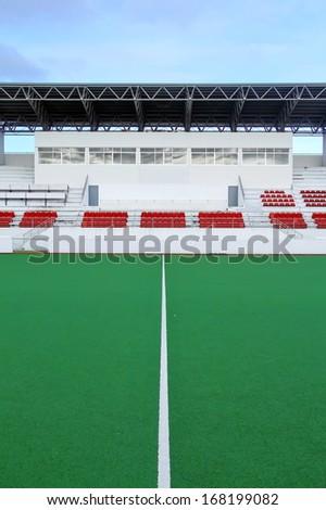 Empty plastic seats at stadium on blue sky - stock photo