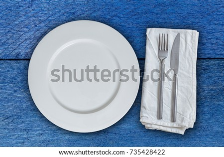 Empty plate and cutlery on blue wood.