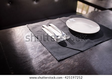 Empty plate and soup spoon on table - stock photo