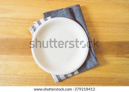 Empty plate and towel over wooden table background. View from above with copy space - stock photo