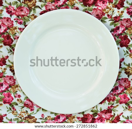 Empty plate at classic tablecloth. - stock photo