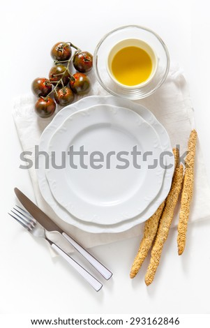 empty plate, black zebra cherry tomato and bread sticks. space for writing text. on white. background for restaurants - stock photo