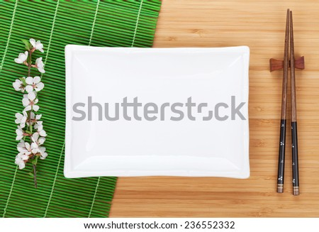 Empty plate, chopsticks and sakura branch over bamboo table - stock photo