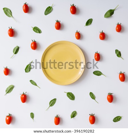 Empty plate concept with cherry tomatoes and basil leaves pattern. Flat lay. - stock photo