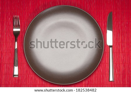 Empty Plate, Fork And Knife On Bamboo Mat