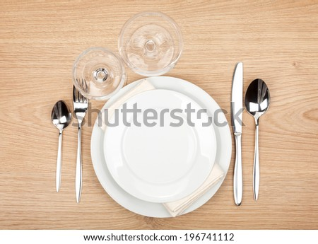 Empty plate, glasses and silverware set on wooden table - stock photo