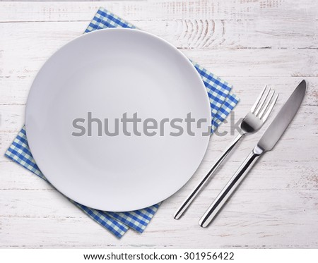 Empty plate, knife, fork and towel over wooden table background. View from top with copy space.