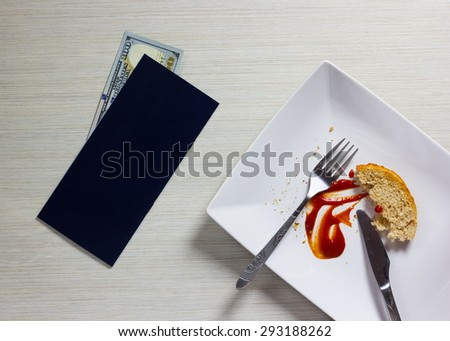 Empty plate left after dinner with bill and Dollars note on wooden table - stock photo
