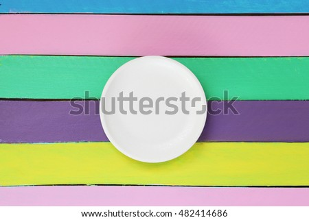 empty plate on colourful wooden table