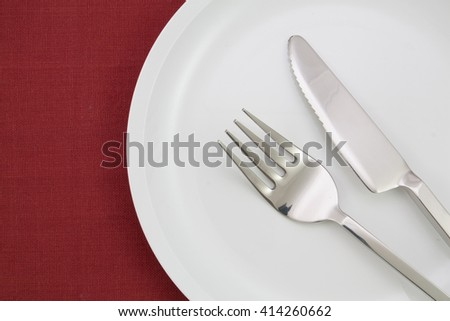 empty plate on red tablecloth