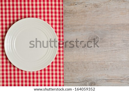 Empty plate on tablecloth on wooden table. Top view. - stock photo