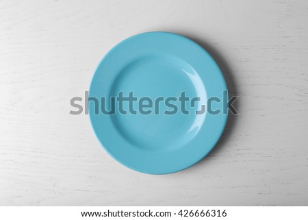 Empty plate on white wooden background - stock photo