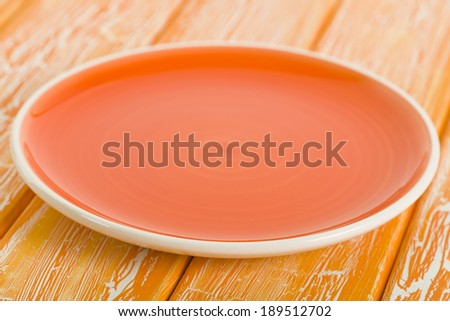 Empty Plate - Orange round empty plate on a crackled orange wooden background. - stock photo