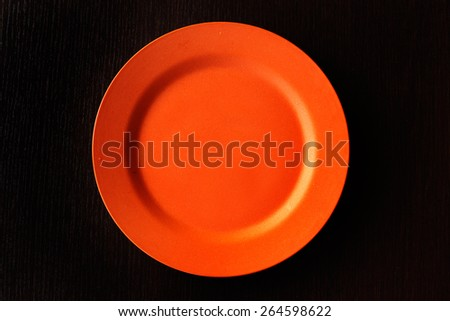 Empty Plate - Orange round empty plate on wooden background. - stock photo