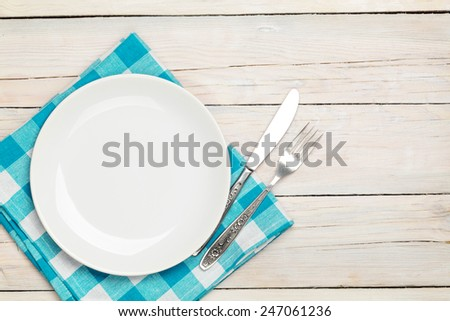 Empty plate, silverware and towel over wooden table background. View from above with copy space - stock photo
