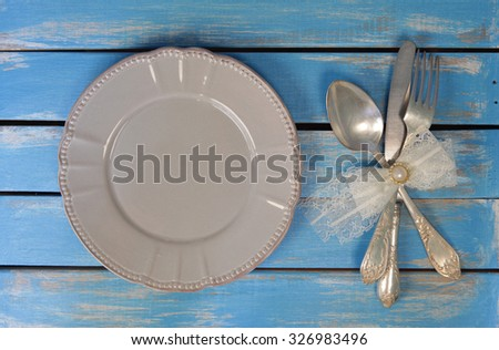 empty plate ,spoon, fork and knife decorated with lace bow knot on rustic wooden background - stock photo