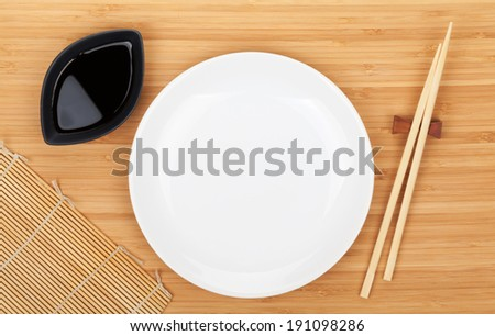 Empty plate, sushi chopsticks and soy sauce on bamboo table - stock photo